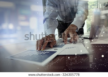 close up of businessman hand working on laptop computer with financial business graph information diagram on wooden desk as concept