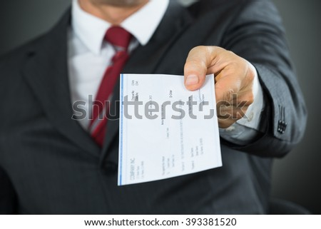 Close-up Of Businessman Hands Giving Cheque In Office - stock photo
