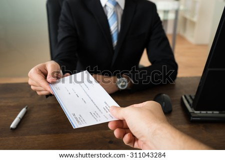 Close-up Of Businessman Hands Giving Cheque To Other Person In Office - stock photo