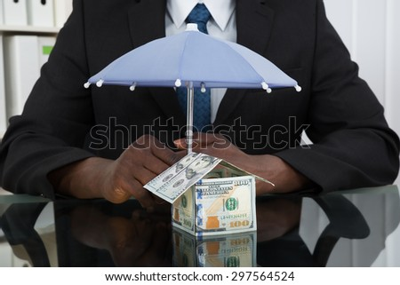 Close-up Of Businessman Hands Protecting House Of Banknote With Umbrella At Desk - stock photo