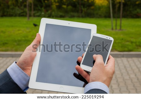 Close up of businessman hands with mobile phone and tablet pc on a park background. Copy space - stock photo