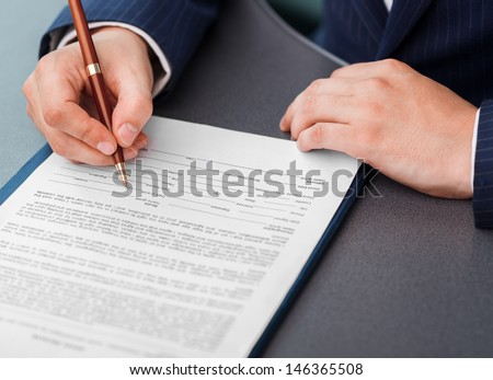 Close-up of businessman hands with pen signing financial document lying on the desk.