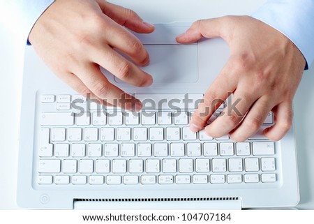 Close-up of businessman hands working with laptop at workplace