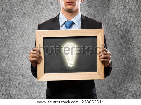 Close up of businessman holding chalkboard with light bulb - stock photo