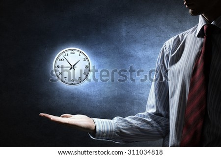 Close up of businessman holding clock sign in palm - stock photo
