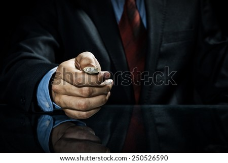 Close up of businessman holding coin in hand - stock photo