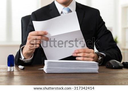 Close-up Of Businessman Holding Document At Desk In Office - stock photo
