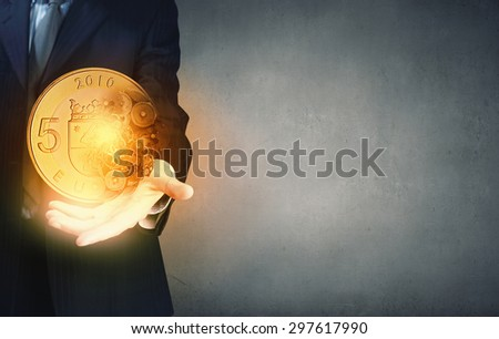 Close up of businessman holding euro coin in hand
