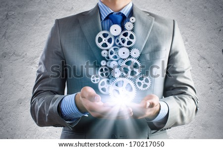 Close up of businessman holding gears in palms - stock photo