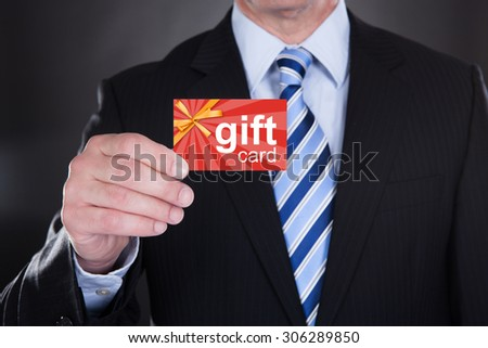 Close-up Of Businessman Holding Gift Card Over Black Background - stock photo