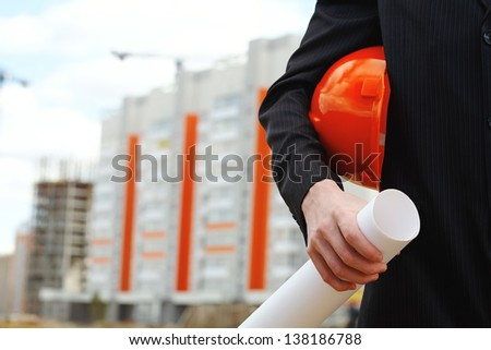 Close-up of businessman holding helmet and building project - stock photo