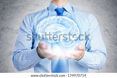 Close up of businessman holding image of brain in hands - stock photo