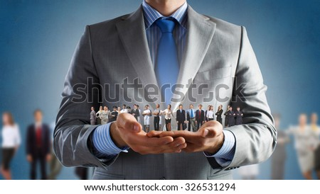 Close up of businessman holding in hands successful people of different professions