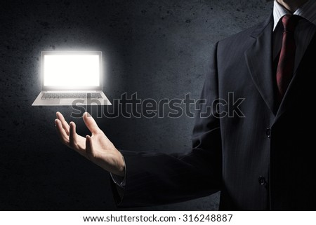 Close up of businessman holding laptop in palm