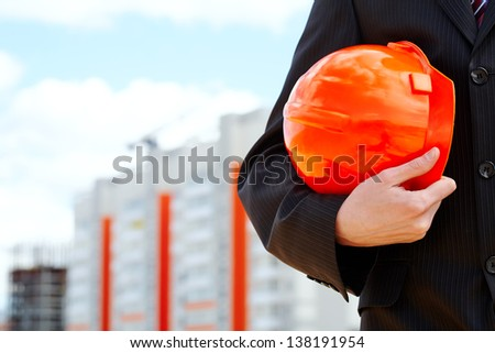 Close-up of businessman holding orange helmet over building construction - stock photo