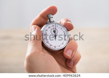 Close-up Of Businessman Holding Stopwatch In Office - stock photo