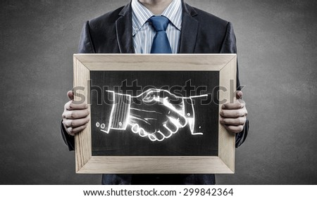 Close up of businessman holding wooden frame with partnership concept - stock photo