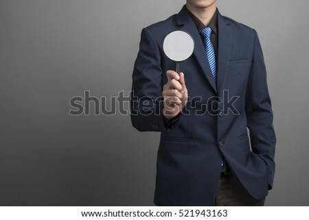 Close up of businessman in blue suit holding magnifier on gray background