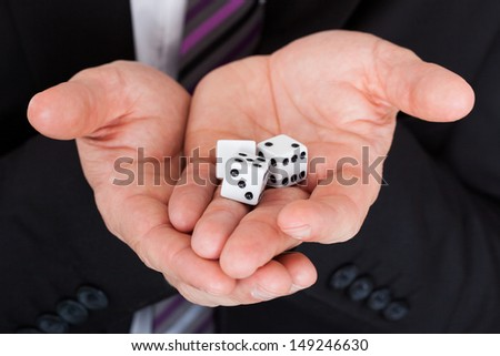 Close up of businessman in suit holding dice - stock photo