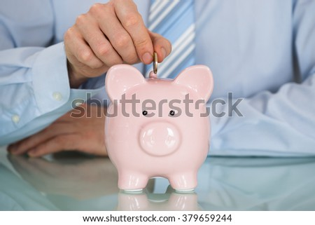 Close-up Of Businessman Inserting Coin In Piggy Bank