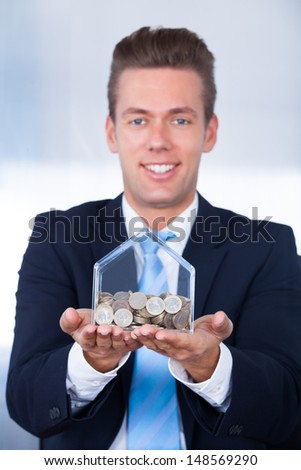 Close-up Of Businessman Inserting Euro Coin In Money Box - stock photo