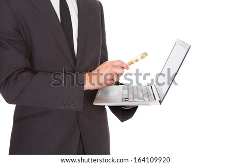 Close-up Of Businessman Looking At Laptop Through Magnifying Glass - stock photo