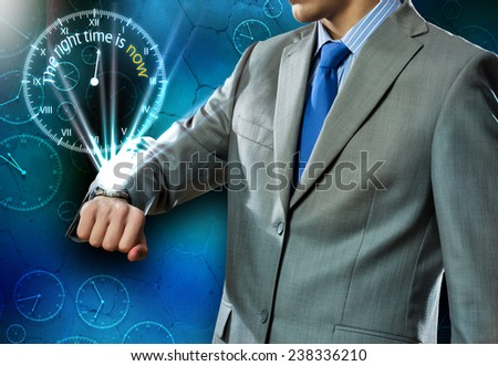 Close up of businessman looking at watch at his wrist - stock photo