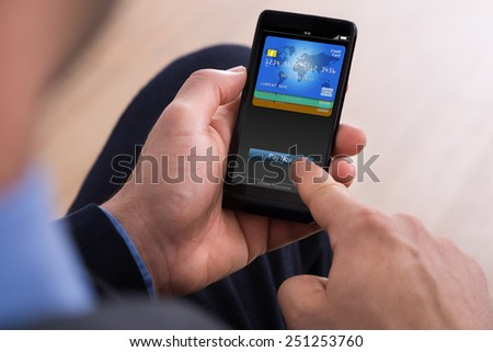 Close-up Of Businessman Making Online Payment On Mobile Phone - stock photo