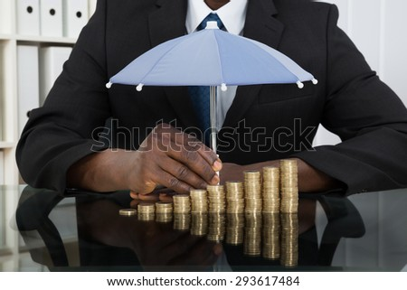Close-up Of Businessman Protecting Stack Of Coins With Umbrella At Desk - stock photo