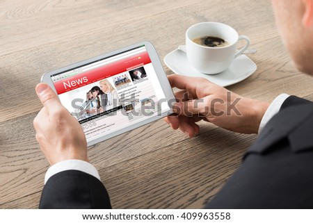 Close-up Of Businessman Reading News On Digital Tablet On Desk At Office - stock photo
