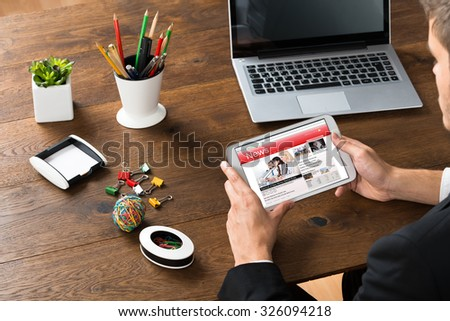 Close-up Of Businessman Reading Online News On Mobile Phone - stock photo