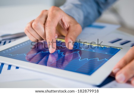 Close Up Of Businessman's Hand Analyzing Graph On Digital Tablet - stock photo