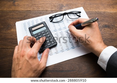 Close-up Of Businessman's Hand Calculating Financial Sheet Using Calculator - stock photo