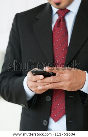 close up of businessman's hands holding cell phone - stock photo