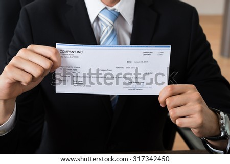 Close-up Of Businessman Showing Signed Cheque In Office - stock photo
