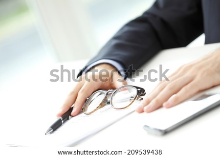 Close-up of businessman sitting at office and fill the form. Business people. - stock photo