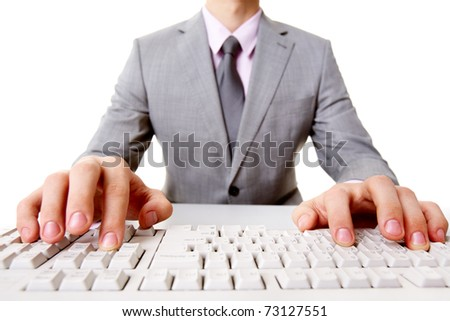 Close-up of businessman sitting at the table and typing - stock photo