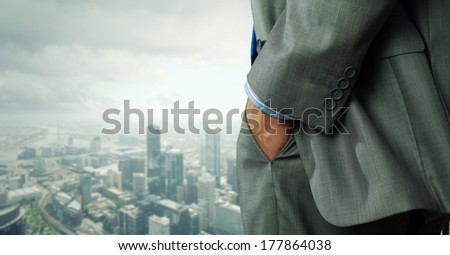 Close up of businessman standing on top viewing at city - stock photo