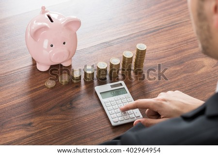 Close-up Of Businessman Using Calculator With Piggybank And Stacked Coins On Desk - stock photo