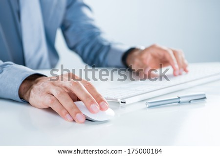 Close Up Of Businessman Using Computer At Desk In Office - stock photo