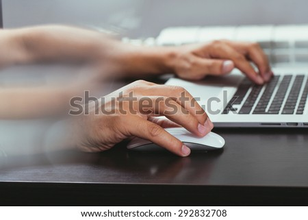 Close up of businessman using computer mouse at desk in office - stock photo