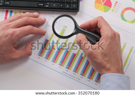 Close up of businessman using loupe for reading chart. Man minutely checking documents with magnifying Glass  - stock photo
