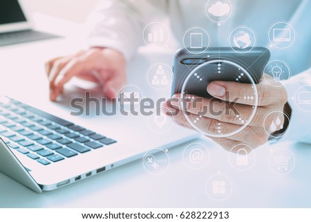 close up of businessman using mobile phone and laptop computer on white desk in modern office with VR icons diagram