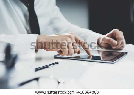 Close-up of businessman using tablet device at his office, male hands share information on internet via digital tablet
