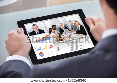 Close-up Of Businessman Video Conferencing With Co-worker About Progress Chart - stock photo
