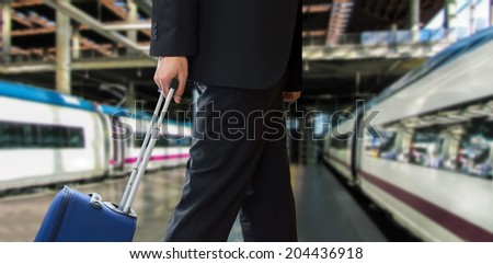 close up of businessman walking travel bag by train station