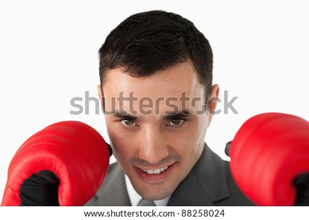 Close up of businessman with boxing gloves on against a white background