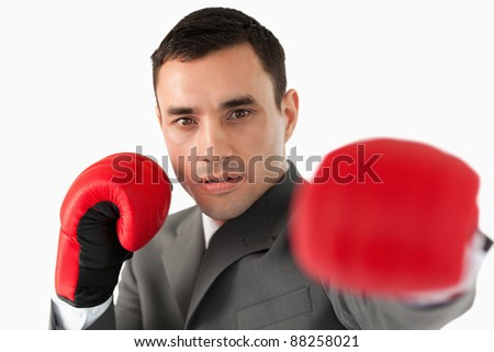 Close up of businessman with boxing gloves slamming against a white background