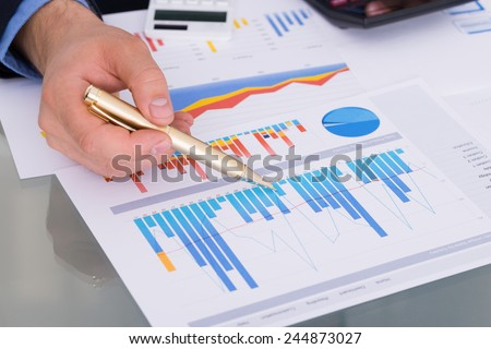 Close-up Of Businessman With Pen And Calculator Analyzing Graph