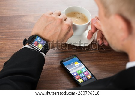 Close-up Of Businessman With Smartphone And Smartwatch Holding Cup Of Coffee On Desk - stock photo